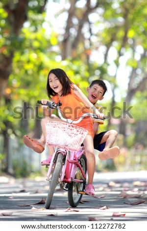 happy smiling little girl and boy riding bicycle together outdoor