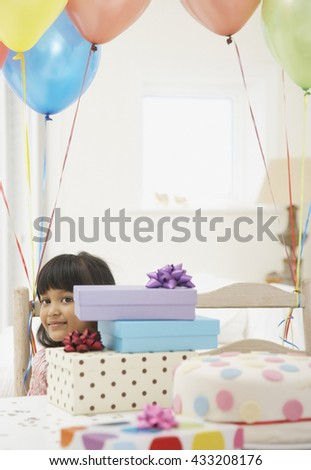 Happy smiling little girl between gifts for birthday - stock photo
