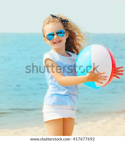 Happy smiling little girl child playing with inflatable water ball on beach over sea summer - stock photo