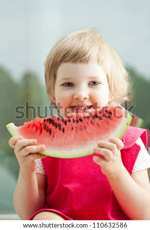 Happy smiling little girl eating big slice of watermelon