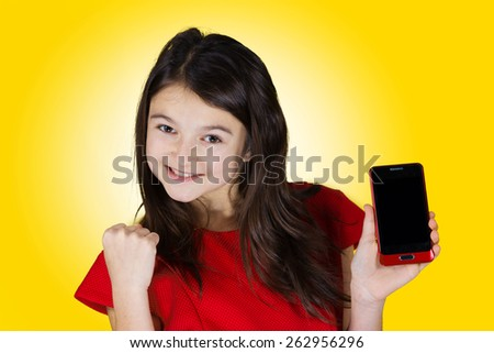 Happy Smiling Little Girl holding mobile phone and gesturing   isolated on yellow background.Success,Communications, - stock photo