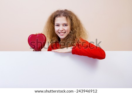 Happy, smiling little girl holding Red heart showing white blank placard, board,poster. - stock photo