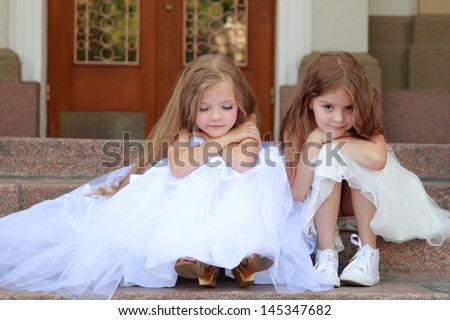 Happy smiling little girl in a white ball gown and sitting on the stairs outdoors - stock photo