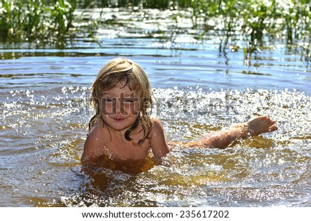 Happy smiling Little girl in water on sunny day