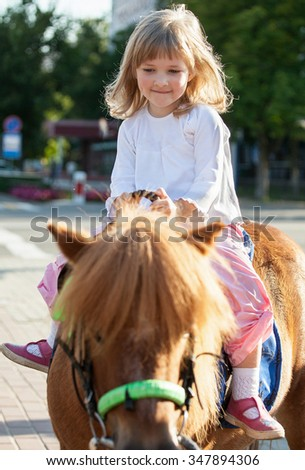Happy smiling little girl on a pony - stock photo