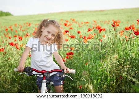 Happy smiling little girl standing bicycle on the poppy meadow - stock photo