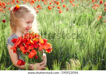 Happy smiling little girl standing on the poppy meadow and holding a posy looking to the side - stock photo