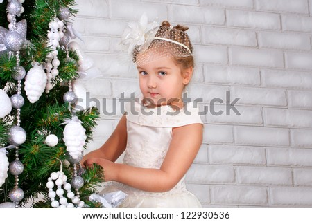 happy smiling little girl with gifts near decorated new year tree - stock photo