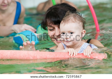 happy smiling little girl with mother swimming at water pool - stock photo