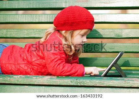 Happy smiling little girl working with tablet pc and lying on bench in the park. - stock photo