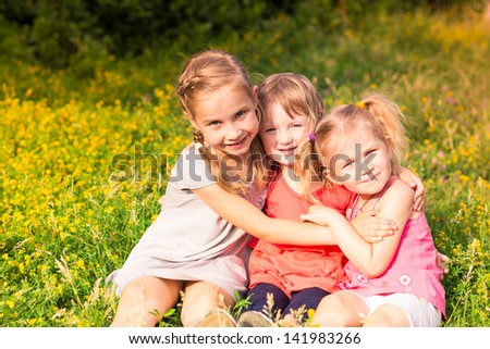 Happy smiling little kids outdoor in the park in summertime