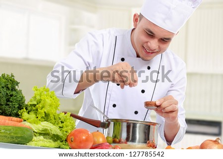 happy smiling male chef put some ingredient in the pan - stock photo