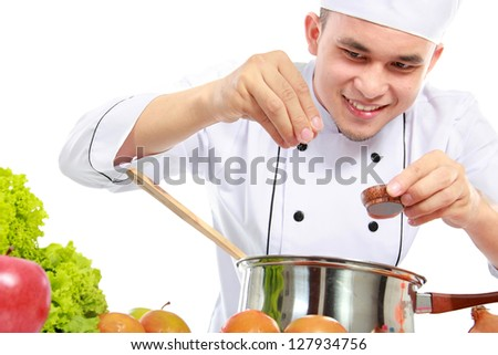 happy smiling male chef put some salt in the pan - stock photo