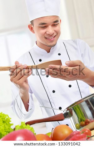 happy smiling male chef taste his cooking in the kitchen - stock photo