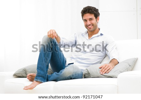 Happy smiling man relaxing and sitting on sofa at home - stock photo