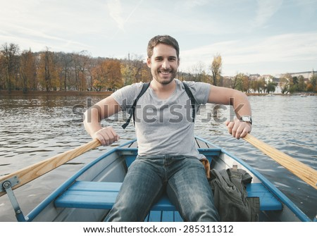 Happy smiling man rowing on the river. retro filter - stock photo