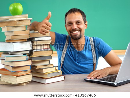 Happy smiling man showing thumbs up gesture. Photo of smiling teacher, creative concept with Back to school theme - stock photo