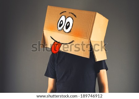 Happy smiling man with cardboard box on his head showing tongue - stock photo