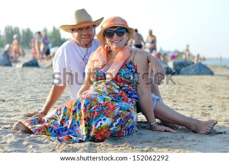 Happy smiling mature couple sitting on sand & looking at camera having fun outdoors on the seashore on sandy beach back to back on holiday - stock photo