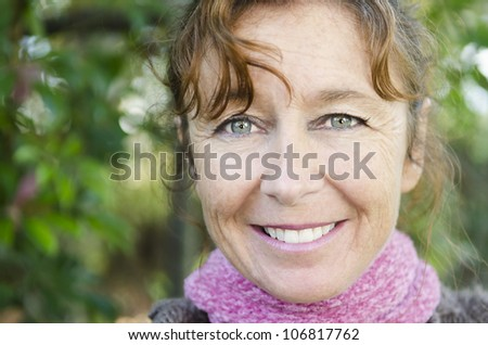 happy smiling mature woman wearing a pink scarf - stock photo