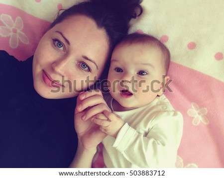 Happy smiling mother and baby lying on bed, top view. Vintage style colored picture