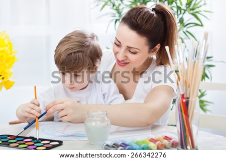 Happy smiling mother and child drawing together with paintbrushes
