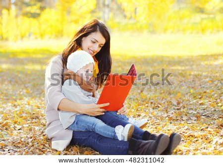 Happy smiling mother and child sits together looking on book or tablet pc in autumn park