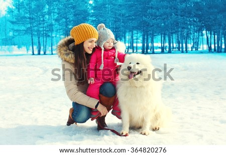 Happy smiling mother and child with white Samoyed dog together in winter day - stock photo