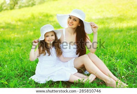 Happy smiling mother and daughter child wearing a white straw hats sitting together on grass in sunny summer day - stock photo