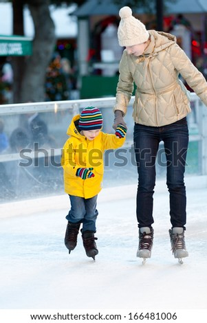 happy smiling mother and her cute cheerful son ice skating together at winter - stock photo