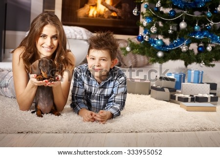Happy smiling mother and son playing with dachshund puppy at christmas time. - stock photo