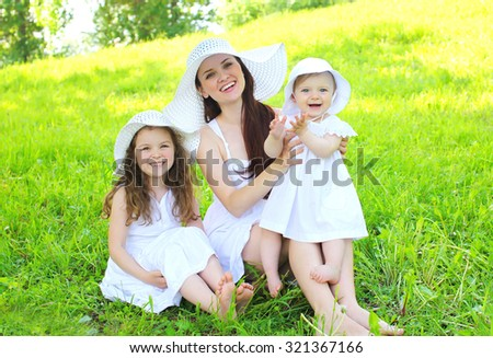 Happy smiling mother and two children wearing white dress and straw hats on grass summer - stock photo