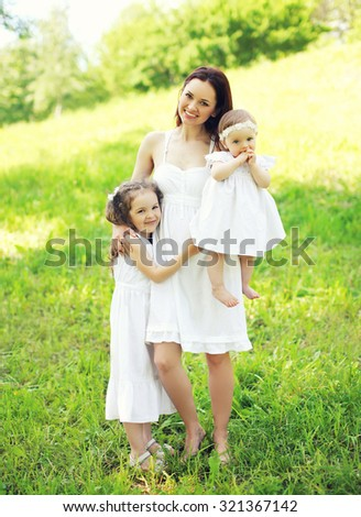 Happy smiling mother hugging two children in sunny summer day