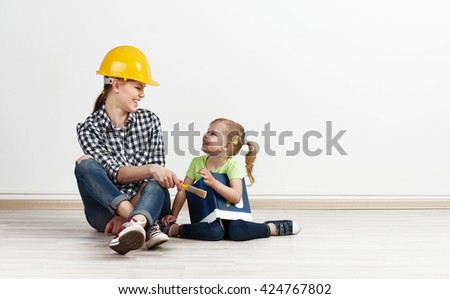 Happy smiling mother in yellow helmet giving paintbrush to her little daughter. Concept of house repair and design.  - stock photo