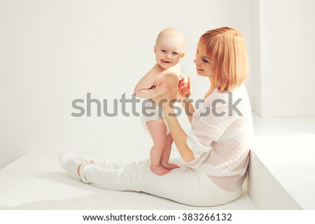 Happy smiling mother playing with baby home in white room near window - stock photo