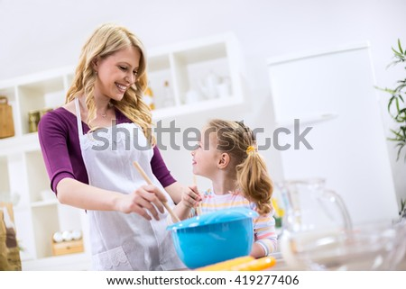 Happy smiling mother teaching child how to baking bread - stock photo