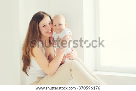 Happy smiling mother with baby at home in white room - stock photo