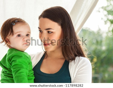 Happy smiling mother with eight months old baby - stock photo