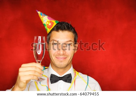Happy smiling new years eve celebrating man with hat on party - stock photo