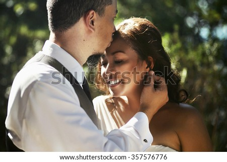 Happy smiling newlyweds walking outdoors, kissing and embracing on their wedding day - stock photo