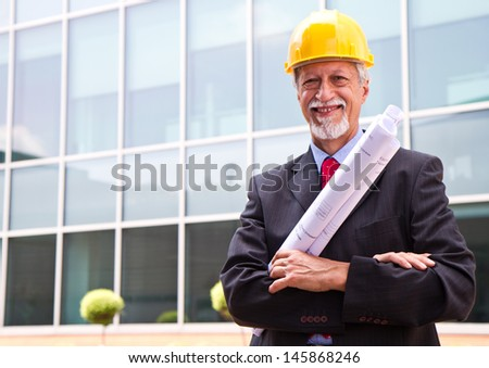 Happy, smiling older architect looking out - stock photo
