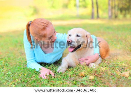 Happy smiling owner woman and Golden Retriever dog lying on grass