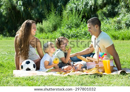 Happy smiling parents with little daughters having holiday with picnic at park