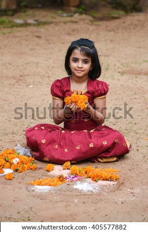 Happy smiling playful young Indian / South Indian girl wearing traditional dress holding flowers both hands for Onam, Vishu Kerala India. Beautiful daughter/ kid in Indian sari. Asian child playing - stock photo