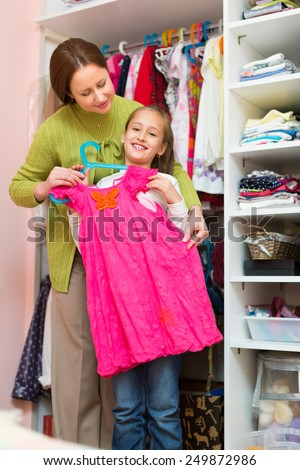 Happy smiling preschooler girl with mom choosing apparel in cloakroom