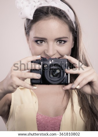 Happy smiling pretty pin up girl with hairband bow taking photo picture with camera. Attractive gorgeous young retro woman photographing.