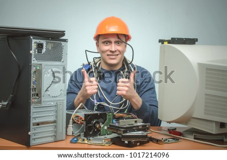 Happy smiling repairman in hard hat is repairing the computer and is showing a thumbs up. Computer technician. PC repair service center.