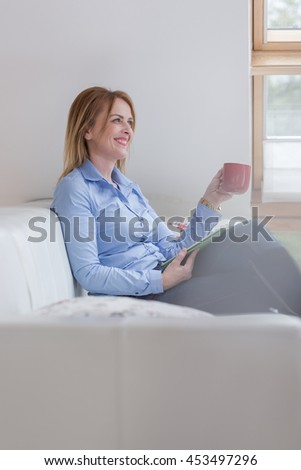Happy smiling rich middle aged business woman 45 yearsusing ipad tablet pc computer reading ebook or emails
