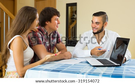 Happy smiling salesman and young couple at home talking about purchase - stock photo