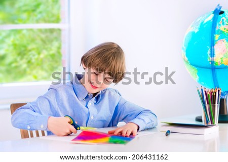 Happy smiling school boy, smart student, doing homework cutting paper, writing, drawing and reading a book at a white desk with a globe next to a window, back to school concept
